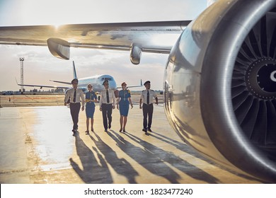 Full length portrait of flight team wearing business uniform walking near the passenger airplane in the outdoors