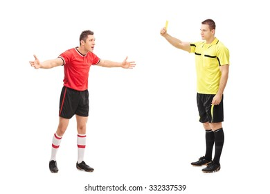 Full length portrait of a football referee showing a yellow card to a displeased player isolated on white background