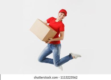 Full length portrait of fun delivery woman in red cap, t-shirt isolated on white background. Female courier or dealer jumping with empty cardboard box. Receiving package. Copy space for advertisement