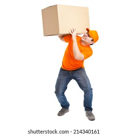 Full length portrait of a funny deliverer lifting an heavy box. Isolated on white