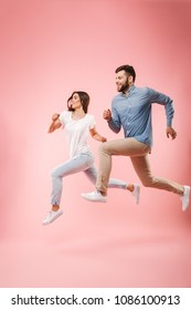 Full length portrait of a funny young couple running fast isolated over pink background