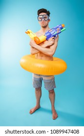 Full length portrait of a funny young shirtless man in swim goggles and inflatable ring having fun with water guns over blue background
