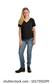 full length portrait of a girl wearing simple black shirt and jeans. standing pose on white studio background.