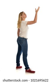 full length portrait of girl wearing white shirt and jeans, standing pose, isolated on white studio background.