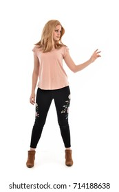 full length portrait of girl wearing simple pink shirt and pants, standing pose on white studio background.