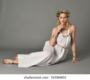 full length portrait of girl wearing white ancient Greek or Roman costume, seated  pose on a grey background.