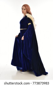 full length portrait of girl wearing long blue velvet gown and fur lined cloak, standing pose  on white background.