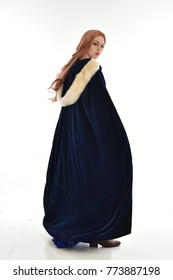 full length portrait of girl wearing long blue velvet gown and fur lined cloak, standing pose  on white background.