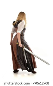 full length portrait of girl wearing brown  fantasy costume and holding a sword. standing pose, view from behind model,  on white background.