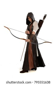 full length portrait of girl wearing brown  fantasy costume, holding a bow and arrow. standing pose on white studio background.
