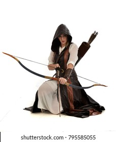 full length portrait of girl wearing brown  fantasy costume, holding a bow and arrow. kneeling pose on white studio background.