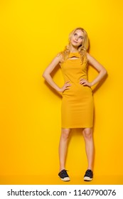 Full length portrait of a girl in a yellow dress. Copy space. Yellow background.