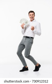 Full length portrait of a glad joyful man in white shirt holding bunch of money banknotes while standing and celebrating isolated over white background