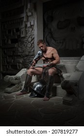 Full length portrait, gladiator in armour sitting on steps of ancient temple looking at sword, on dark background. Concept of masculine power, strength
