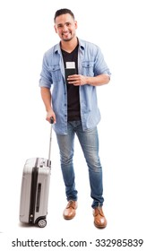 Full length portrait of a good looking guy carrying a suitcase and his passport before going on vacation