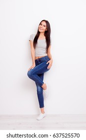 Full length portrait of gorgeous playful lady. She is wearing casual outfit and stands on pure white background