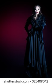 Full length portrait of a gorgeous vampire woman in black medieval dress over dark bloody  background. Halloween.