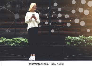 Full length portrait of gorgeous young woman holding smartphone in the hand and looking to infographics design elements of networking connection ,female hipster chatting with friend via mobile phone