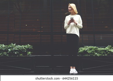 Full length portrait of gorgeous young woman holding smartphone in the hand and looking to the empty copy space area for your text message or information,female hipster have chat conversation on phone