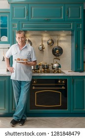 Full length portrait of a granddad holding a plate of homemade muffins. Kitchen background. Baking hobby, retirement.