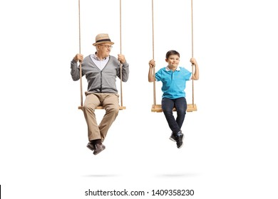 Full length portrait of a grandfather looking at his grandson and sitting on wooden swings isolated on white background
