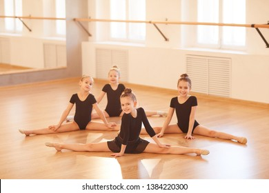 Full length portrait of group of little girls stretching legs during warm up at balet practice, lit by sunlight