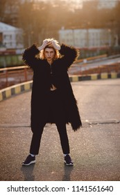 Full length portrait of grunge hipster woman with blonde hair, colorful make up in black fur outfit standing on the road in urban zone on sunset.