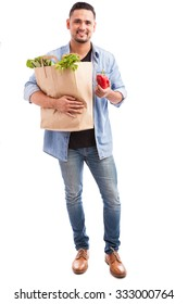 Full length portrait of a guy carrying a bag of groceries and holding a bell pepper in one hand