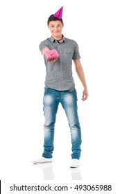Full length portrait of a guy with party hat, isolated on white background. Teen student boy with birthday cap. Portrait of young man gives present wrapped in pink paper with bow.