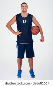 Full length portrait of a handsome basketball player standing isolated on a white background and looking at camera
