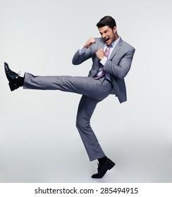 Full length portrait of handsome businessman kicking over gray background