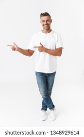 Full length portrait of a handsome casual man standing isolated over white background, presenting copy space, pointing