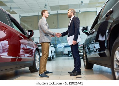 Full length portrait of  handsome client shaking hands with mature sales manager in car showroom, after buying brand new luxury car