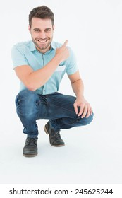 Full length portrait of handsome delivery man crouching while pointing backward on white background