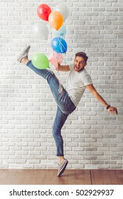 Full length portrait of handsome guy in casual clothes holding balloons, jumping and smiling, on white brick wall background