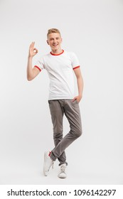 Full length portrait of handsome hipster boy wearing casual clothing smiling and showing ok sign to you isolated over white background