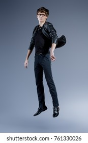 Full length portrait of a handsome male model in leather jacket and jeans posing in a motion. Male beauty, fashion. Studio shot.