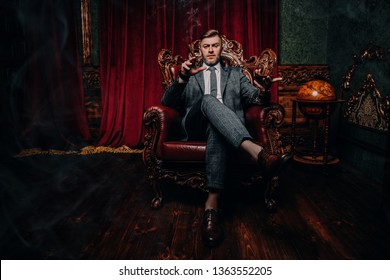 A full length portrait of a handsome mature man in a formal costume sitting in the armchair in the classic interior. Men's beauty, fashion.
