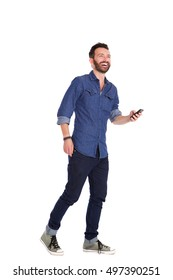 Full length portrait of handsome mature man walking with mobile phone and laughing over white background