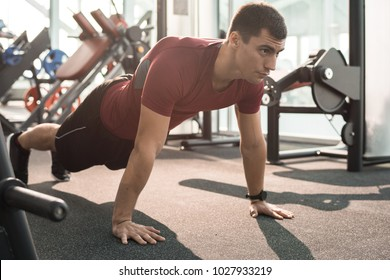 Full length portrait of handsome muscular man doing push ups training in modern gym