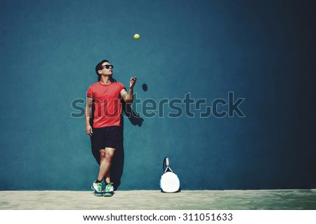 Full length portrait of handsome sportsman tossing a tennis ball while taking break after paddle game in sunny day outdoors, paddle player with copy space area for text message or advertising content