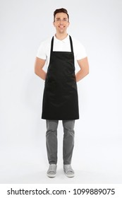 Full length portrait of handsome waiter in apron on light background