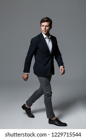 Full length portrait of a handsome young businessman dressed in suit isolated over gray background, posing, looking away, walking