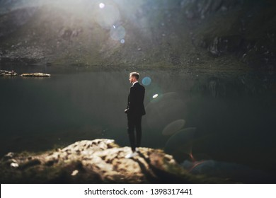 Full length portrait of a handsome young caucasian man dressed in suit sitting on a rock in the mountains near a lake against sunrise looking away.