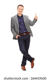 Full length portrait of a handsome young man leaning against a wall and giving a thumb up isolated on white background