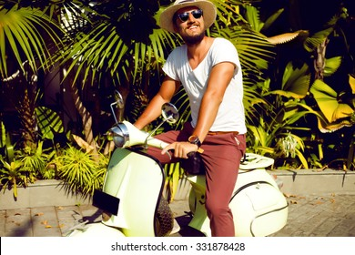 Full length portrait of a handsome young man enjoy his days,ride vintage vespa on the city,Casual man posing outdoor on the street,palms background.Street style,mans fashion.hand watch,mans hat,pastel