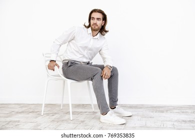 Full length portrait of a handsome young man on a chair. Male beauty, fashion. Furniture, interior concept.