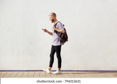 Full length portrait of handsome young man walking with cell phone