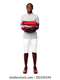 Full length portrait of a happy african man holding his clothes over white background
