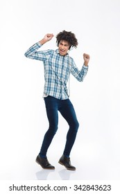 Full length portrait of a happy afro american man listening  music in headphones and dancing isolated on a white background